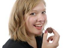 Mujer joven sonriente que come un caramelo de chocolate Imagen de archivo libre de regalías
