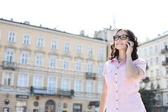 Mujer joven sonriente que contesta al teléfono elegante contra el edificio el día soleado fotos de archivo