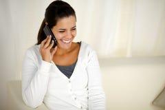 Mujer joven sonriente que conversa en el teléfono móvil Imagen de archivo