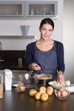 Mujer joven sonriente que cuece una tarta de la manzana Imagen de archivo libre de regalías