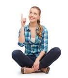 Mujer joven sonriente que destaca el finger Imagen de archivo libre de regalías