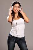 Mujer joven sonriente que disfruta de música en los auriculares Foto de archivo