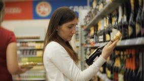 Mujer joven sonriente que elige una botella de vino rojo almacen de metraje de vídeo