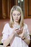Mujer joven sonriente que envía un mensaje de texto en casa Fotos de archivo libres de regalías
