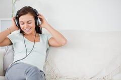 Mujer joven sonriente que escucha la música Imágenes de archivo libres de regalías