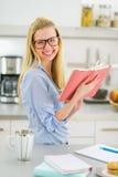 Mujer joven sonriente que estudia en cocina Imágenes de archivo libres de regalías
