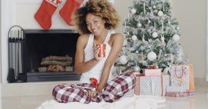 Mujer joven sonriente que goza de una taza de café de Navidad almacen de metraje de vídeo