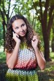 Mujer joven sonriente que habla al aire libre móvil Imagenes de archivo