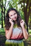 Mujer joven sonriente que habla al aire libre móvil Imagen de archivo libre de regalías