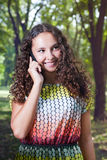 Mujer joven sonriente que habla al aire libre móvil Imágenes de archivo libres de regalías