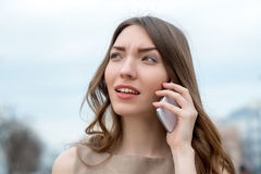 Mujer joven sonriente que habla en el teléfono celular Imagenes de archivo