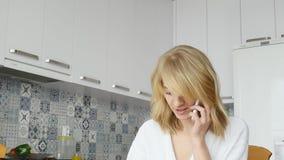 Mujer joven sonriente que habla en el teléfono móvil mientras que desayunando en una cocina almacen de video