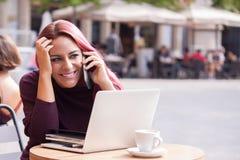 Mujer joven sonriente que habla en el teléfono y la consumición de un café s Fotografía de archivo
