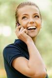 Mujer joven sonriente que habla en la célula Foto de archivo