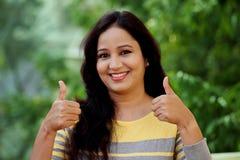 Mujer joven sonriente que hace el pulgar encima del gesto en al aire libre Imágenes de archivo libres de regalías