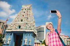 Mujer joven sonriente que hace el selfie cerca del templo de Sri Mariamman, Singapur Foto de archivo
