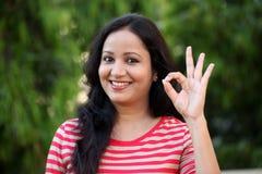 Mujer joven sonriente que hace gesto ACEPTABLE Imagen de archivo libre de regalías