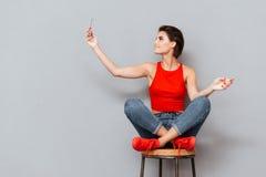 Mujer joven sonriente que hace la foto del selfie en smartphone Imágenes de archivo libres de regalías
