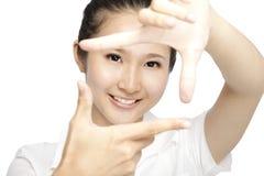 Mujer joven sonriente que hace un marco de la mano fotos de archivo libres de regalías