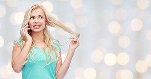 Mujer joven sonriente que invita a smartphone Foto de archivo libre de regalías