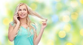 Mujer joven sonriente que invita a smartphone Imagen de archivo libre de regalías