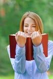 Mujer joven sonriente que lee el libro rojo Foto de archivo libre de regalías