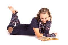 Mujer joven sonriente que lee un libro Imagenes de archivo