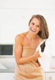 Mujer joven sonriente que limpia el pelo con la toalla Fotos de archivo