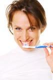 Mujer joven sonriente que limpia sus dientes Imágenes de archivo libres de regalías