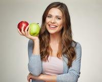 Mujer joven sonriente que lleva a cabo dos manzanas, rojos y verdes Imagen de archivo libre de regalías