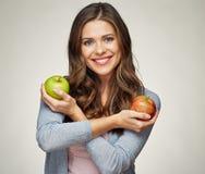 Mujer joven sonriente que lleva a cabo dos manzanas, rojos y verdes Foto de archivo