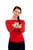 Mujer joven sonriente que lleva a cabo el modelo de la casa Imagenes de archivo