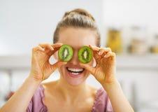 Mujer joven sonriente que lleva a cabo rebanadas del kiwi delante de ojos Fotografía de archivo libre de regalías