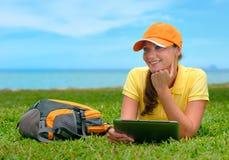 Mujer joven sonriente que miente en el césped con la mochila y la tableta c Foto de archivo
