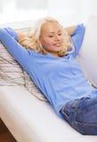 Mujer joven sonriente que miente en el sofá en casa Imagen de archivo