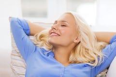 Mujer joven sonriente que miente en el sofá en casa Imagen de archivo libre de regalías