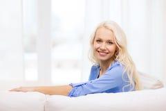 Mujer joven sonriente que miente en el sofá en casa Fotos de archivo libres de regalías