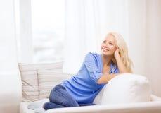 Mujer joven sonriente que miente en el sofá en casa Imagenes de archivo