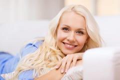 Mujer joven sonriente que miente en el sofá en casa Foto de archivo