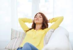 Mujer joven sonriente que miente en el sofá en casa Fotos de archivo