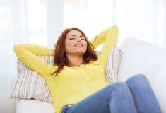 Mujer joven sonriente que miente en el sofá en casa Imágenes de archivo libres de regalías