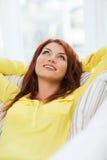 Mujer joven sonriente que miente en el sofá en casa Fotografía de archivo