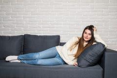 Mujer joven sonriente que miente en el sofá en casa Fotografía de archivo libre de regalías