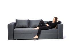 Mujer joven sonriente que miente en el sofá en el fondo blanco Imagen de archivo