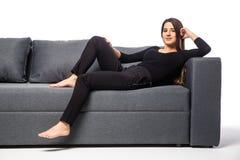 Mujer joven sonriente que miente en el sofá en el fondo blanco Fotos de archivo
