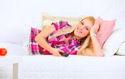 Mujer joven sonriente que miente en el sofá y la TV de observación Imagen de archivo libre de regalías
