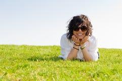 Mujer joven sonriente que miente en la hierba Foto de archivo