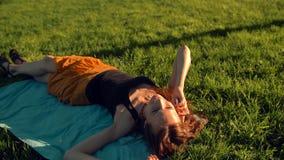 Mujer joven sonriente que miente en la hierba y que habla por el teléfono almacen de metraje de vídeo