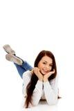 Mujer joven sonriente que miente en piso Imágenes de archivo libres de regalías