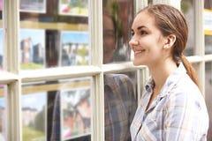 Mujer joven sonriente que mira en la ventana de agentes de la propiedad inmobiliaria foto de archivo libre de regalías